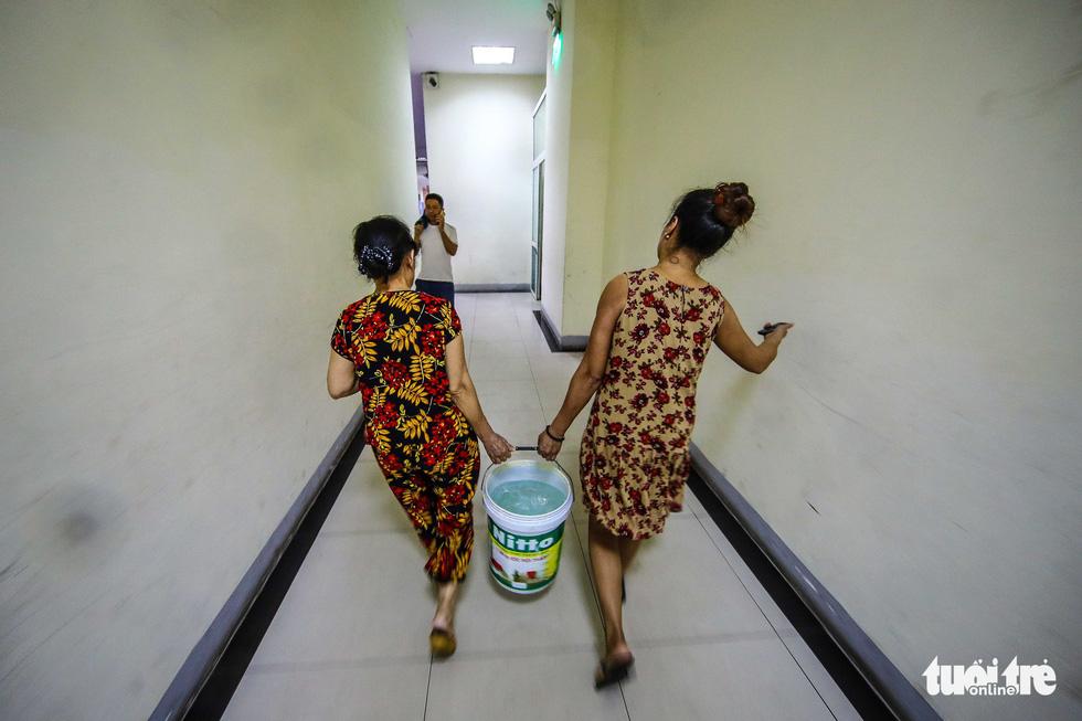 Người dân Hà Nội đội mưa hứng nước sạch - Ảnh 8.