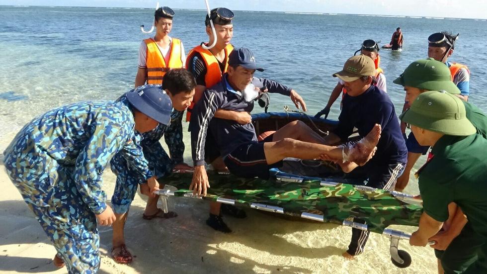Cán bộ, chiến sỹ đưa ngư dân Long lên đảo để chữa trị - Ảnh: NGUYỄN NINH