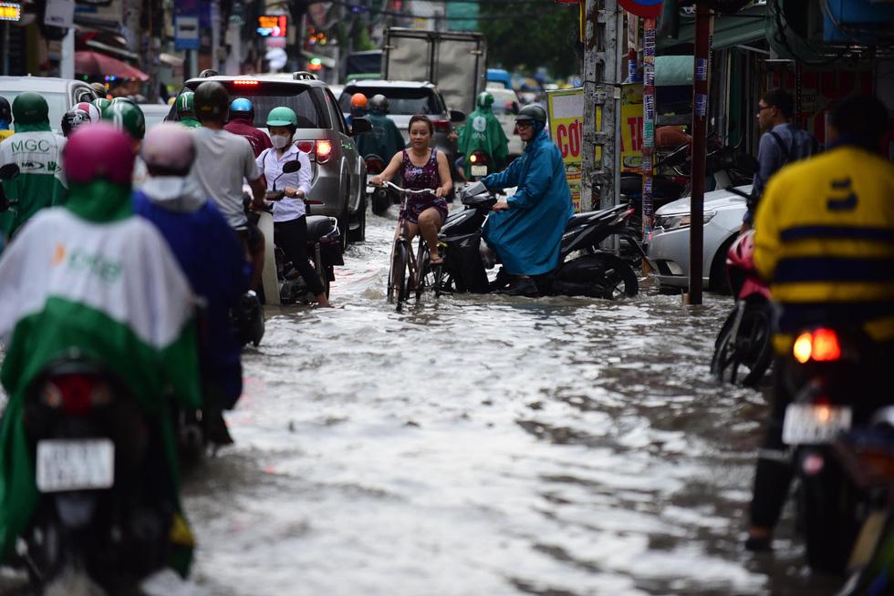 Người dân TP.HCM vật lộn trong mưa đầu mùa gây ngập nửa mét - Ảnh 11.