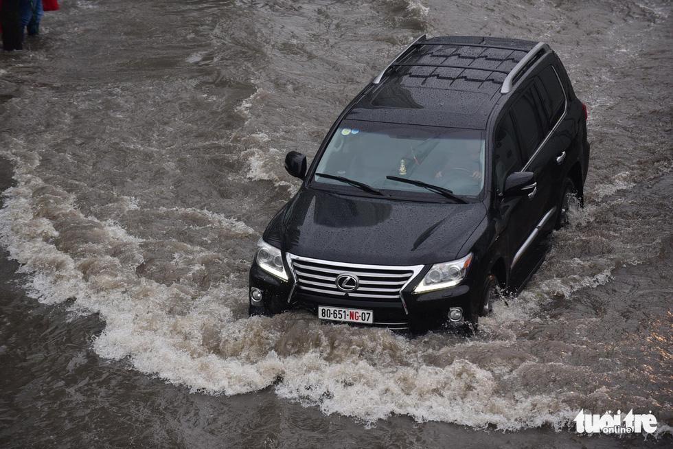 Người dân TP.HCM vật lộn trong mưa đầu mùa gây ngập nửa mét - Ảnh 2.