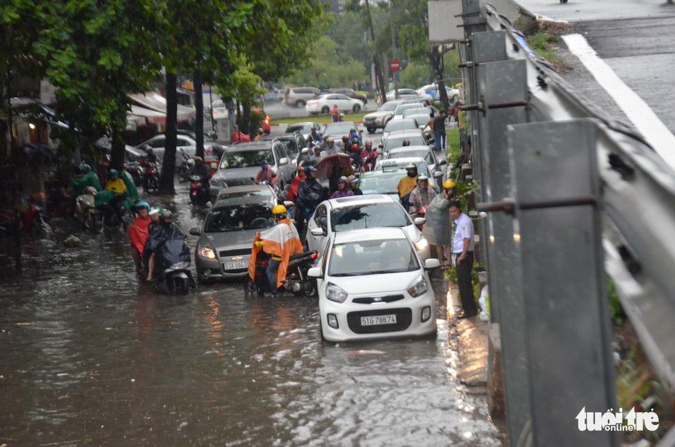 Người dân TP.HCM vật lộn trong mưa đầu mùa gây ngập nửa mét - Ảnh 3.