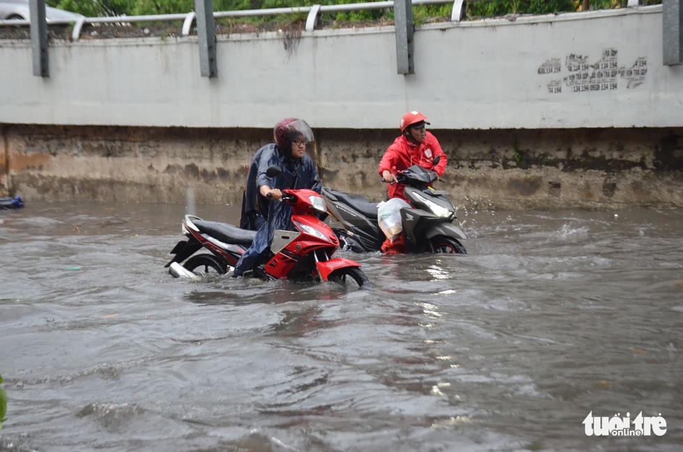 Người dân TP.HCM vật lộn trong mưa đầu mùa gây ngập nửa mét - Ảnh 5.