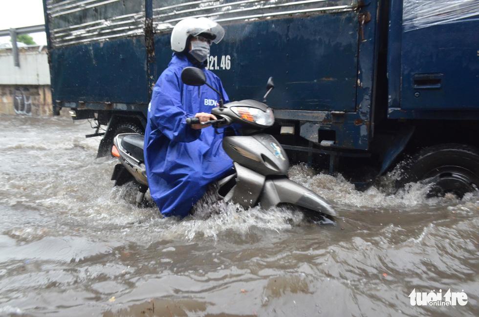 Người dân TP.HCM vật lộn trong mưa đầu mùa gây ngập nửa mét - Ảnh 7.