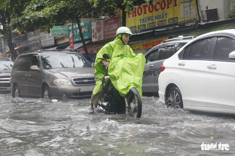 Người dân TP.HCM vật lộn trong mưa đầu mùa gây ngập nửa mét - Ảnh 8.