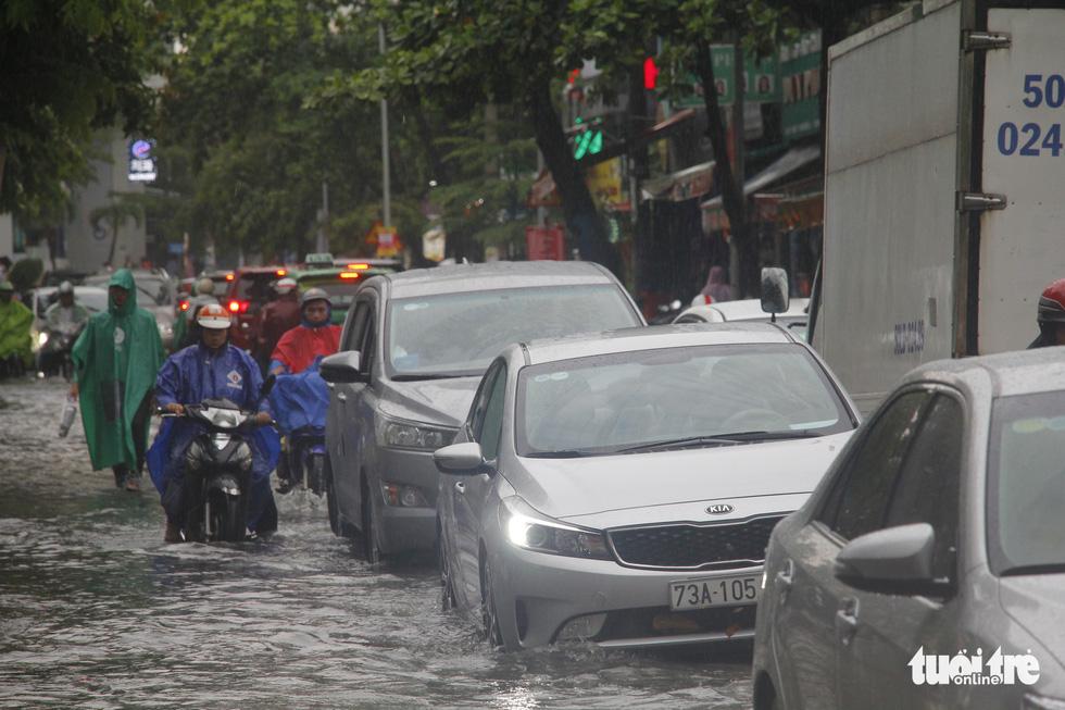 Người dân TP.HCM vật lộn trong mưa đầu mùa gây ngập nửa mét - Ảnh 9.
