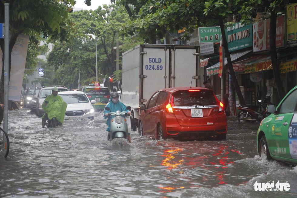 Người dân TP.HCM vật lộn trong mưa đầu mùa gây ngập nửa mét - Ảnh 10.