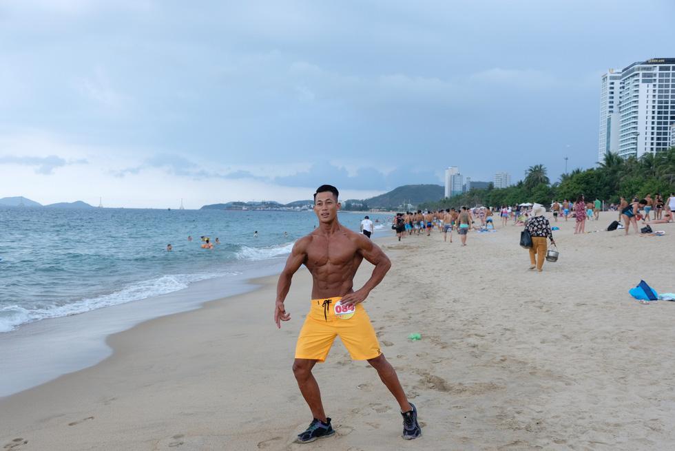 100 vận động viên biểu diễn cơ thể cường tráng bên bờ biển - Ảnh 9.