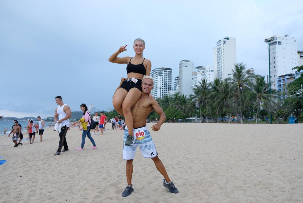 100 vận động viên biểu diễn cơ thể cường tráng bên bờ biển - Ảnh 8.
