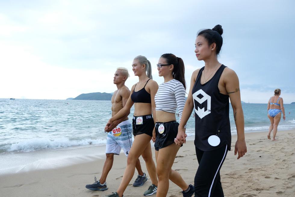 100 vận động viên biểu diễn cơ thể cường tráng bên bờ biển - Ảnh 2.