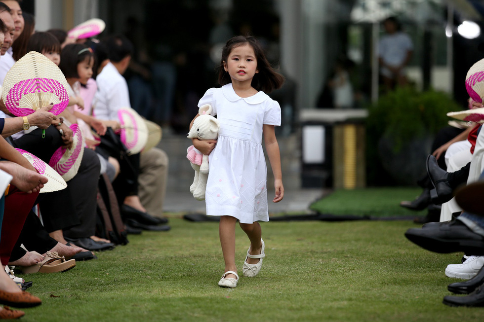 Mẫu nhí ngậm bình sữa, ôm gấu diễn thời trang cùng HHen Niê - Ảnh 6.