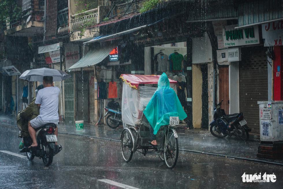 Mưa bão vẫn ráng mưu sinh ở Hà Nội - Ảnh 2.