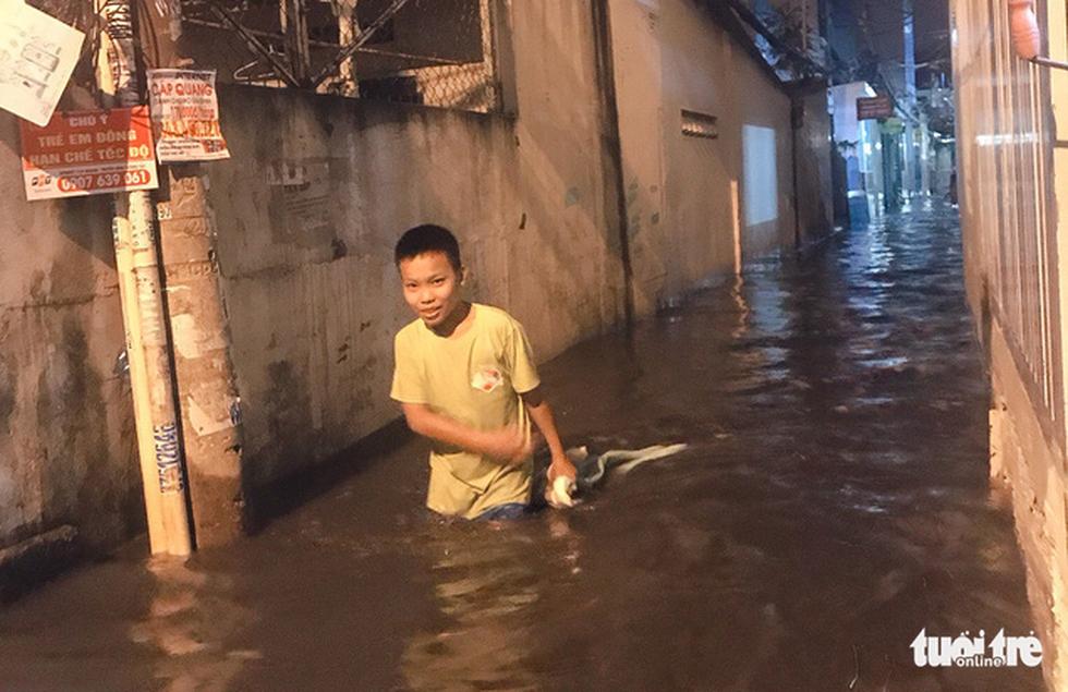 Vỡ bờ bao tại quận 8, hàng trăm hộ dân ngập chìm trong nước - Ảnh 2.