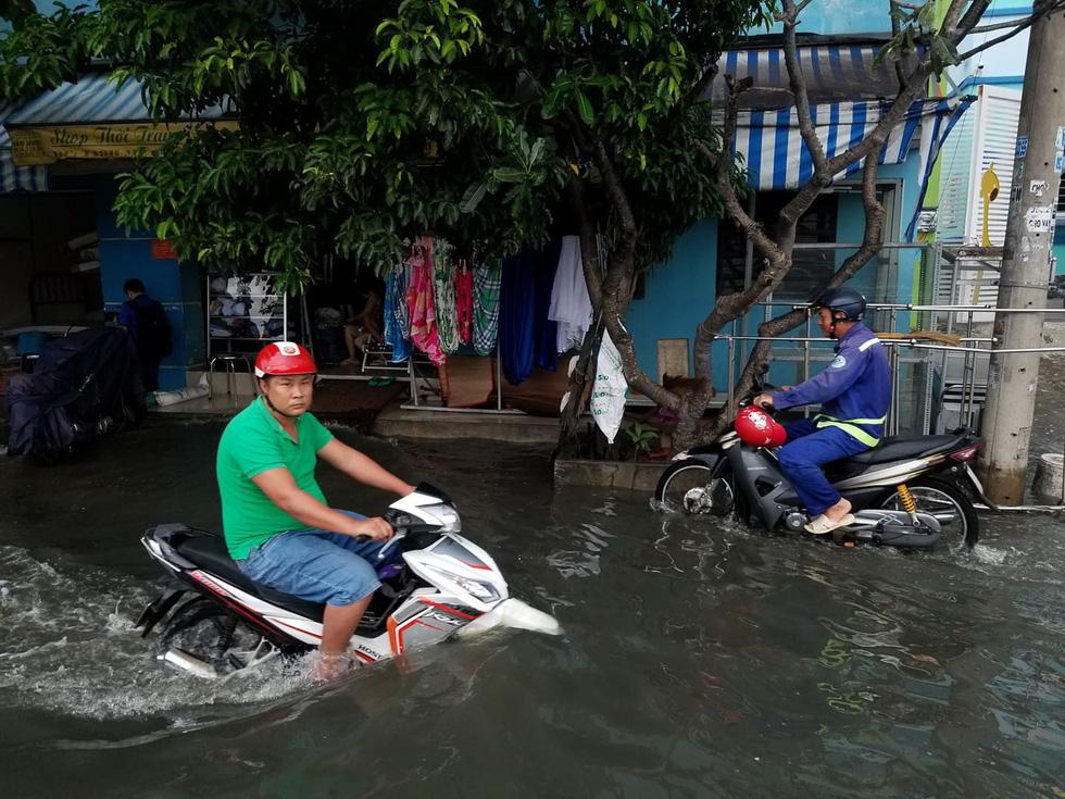 Triều cường kỷ lục, nước sông nước cống bủa vây nhiều tuyến đường TP.HCM - Ảnh 6.