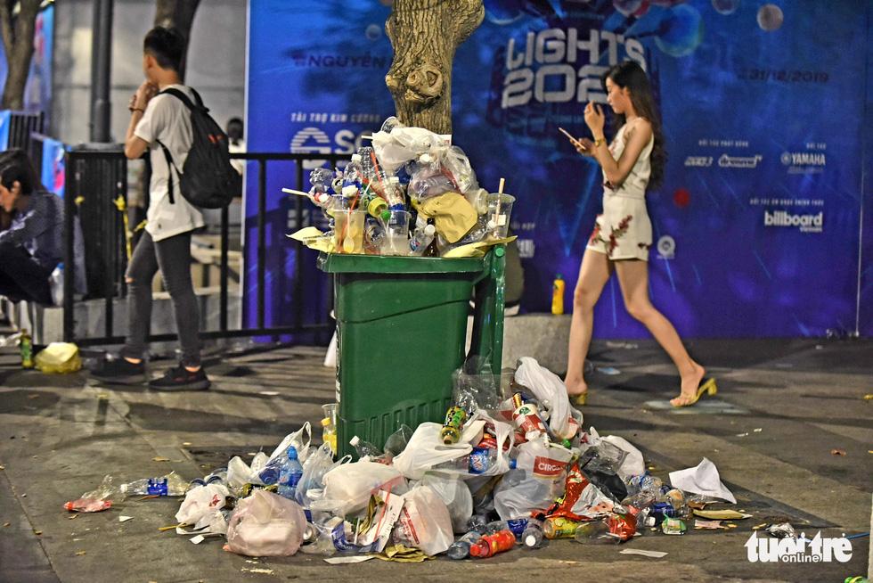 Phố đi bộ Nguyễn Huệ vẫn tràn ngập rác thải sau giao thừa - Ảnh 6.