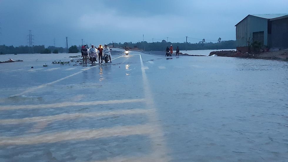 Nước lũ tràn qua quốc lộ 1 vào nhà dân, công an đội mưa điều tiết giao thông - Ảnh 4.