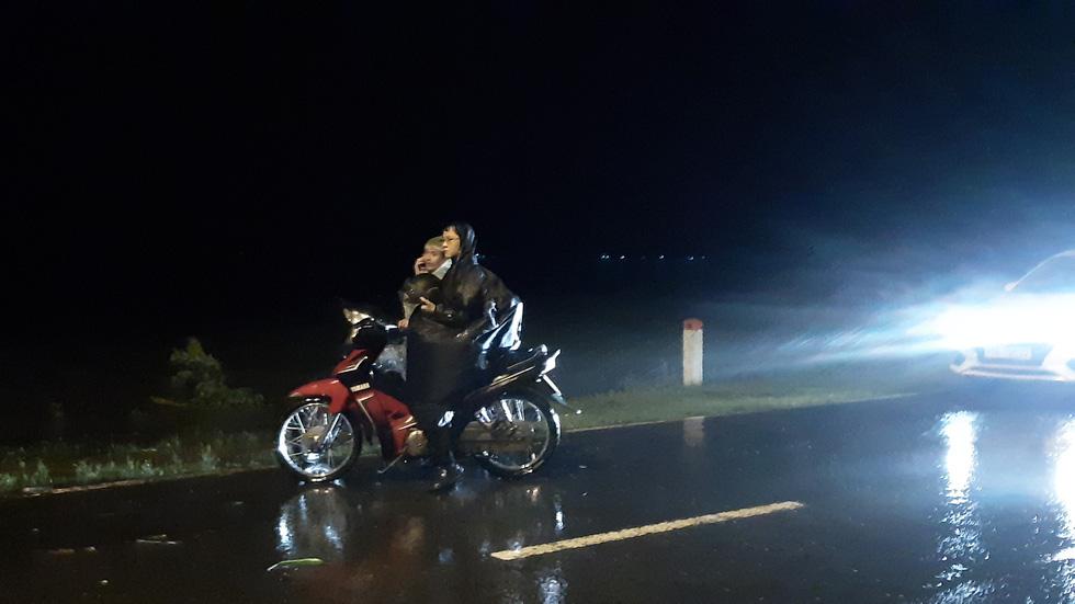 Nước lũ tràn qua quốc lộ 1 vào nhà dân, công an đội mưa điều tiết giao thông - Ảnh 5.