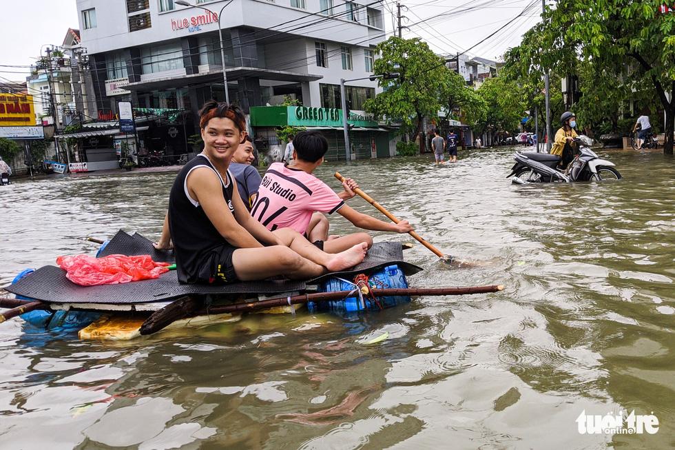 Nước lên nhanh, người dân bắt thuyền máy đi giữa TP Huế - Ảnh 4.