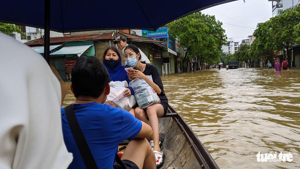 Nước lên nhanh, người dân bắt thuyền máy đi giữa TP Huế - Ảnh 2.