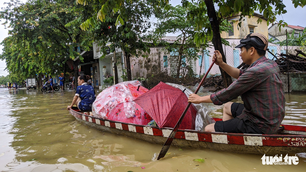 Nước lên nhanh, người dân bắt thuyền máy đi giữa TP Huế - Ảnh 7.