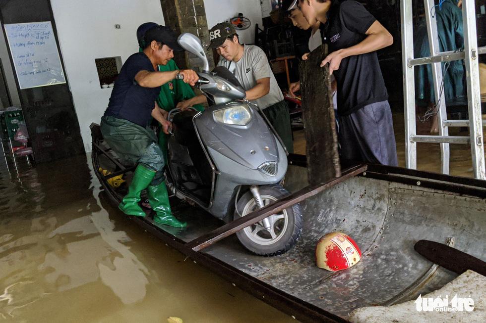 Nước lên nhanh, người dân bắt thuyền máy đi giữa TP Huế - Ảnh 9.