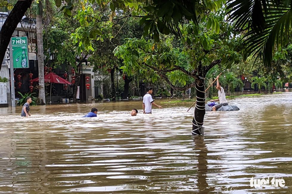Nước lên nhanh, người dân bắt thuyền máy đi giữa TP Huế - Ảnh 10.
