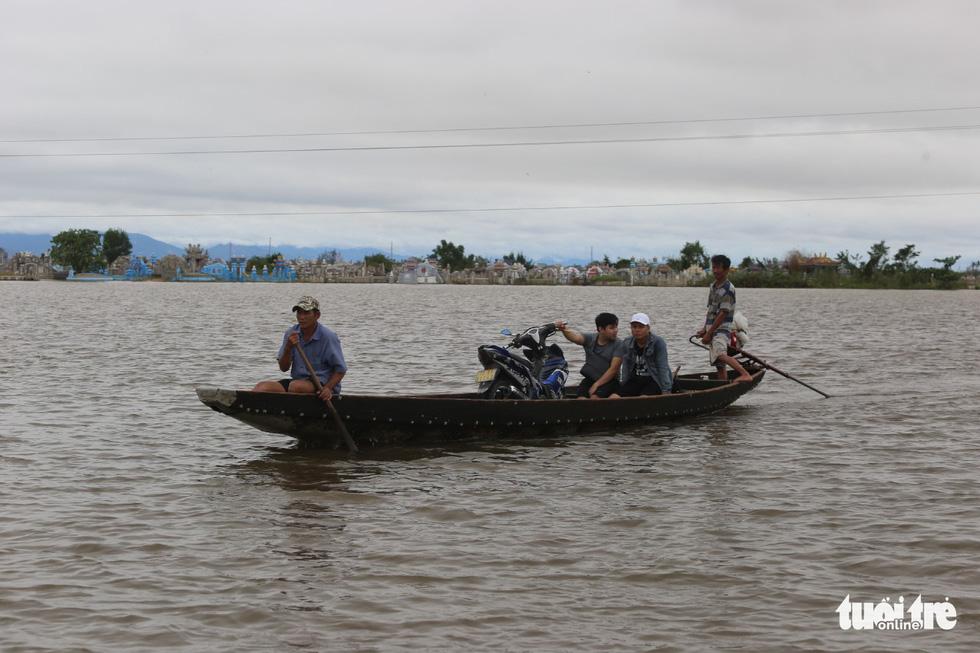 Huế nhiều xã vẫn ngập sâu, người dân chèo thuyền đi nhận cứu trợ - Ảnh 9.