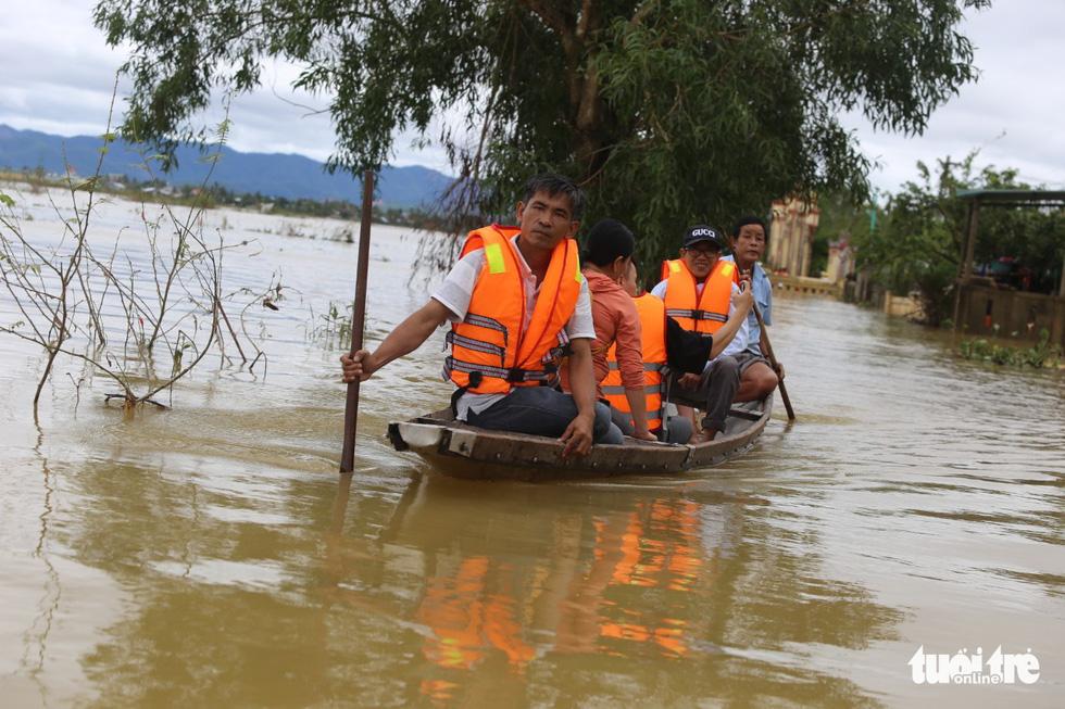 Huế nhiều xã vẫn ngập sâu, người dân chèo thuyền đi nhận cứu trợ - Ảnh 5.