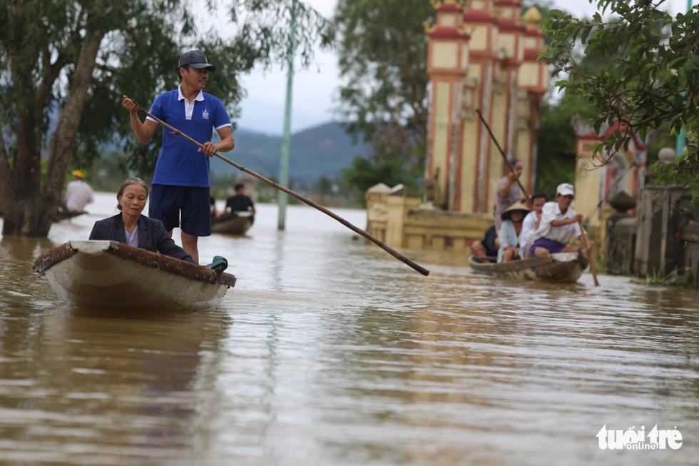 Huế nhiều xã vẫn ngập sâu, người dân chèo thuyền đi nhận cứu trợ - Ảnh 3.