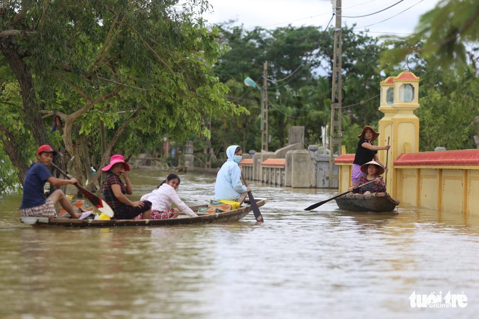 Huế nhiều xã vẫn ngập sâu, người dân chèo thuyền đi nhận cứu trợ - Ảnh 4.