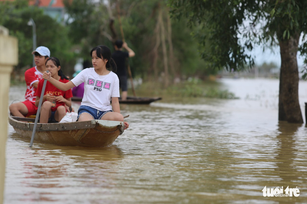 Huế nhiều xã vẫn ngập sâu, người dân chèo thuyền đi nhận cứu trợ - Ảnh 6.