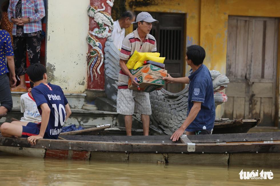 Huế nhiều xã vẫn ngập sâu, người dân chèo thuyền đi nhận cứu trợ - Ảnh 7.