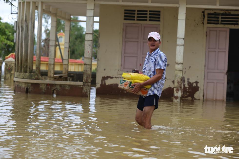 Huế nhiều xã vẫn ngập sâu, người dân chèo thuyền đi nhận cứu trợ - Ảnh 8.