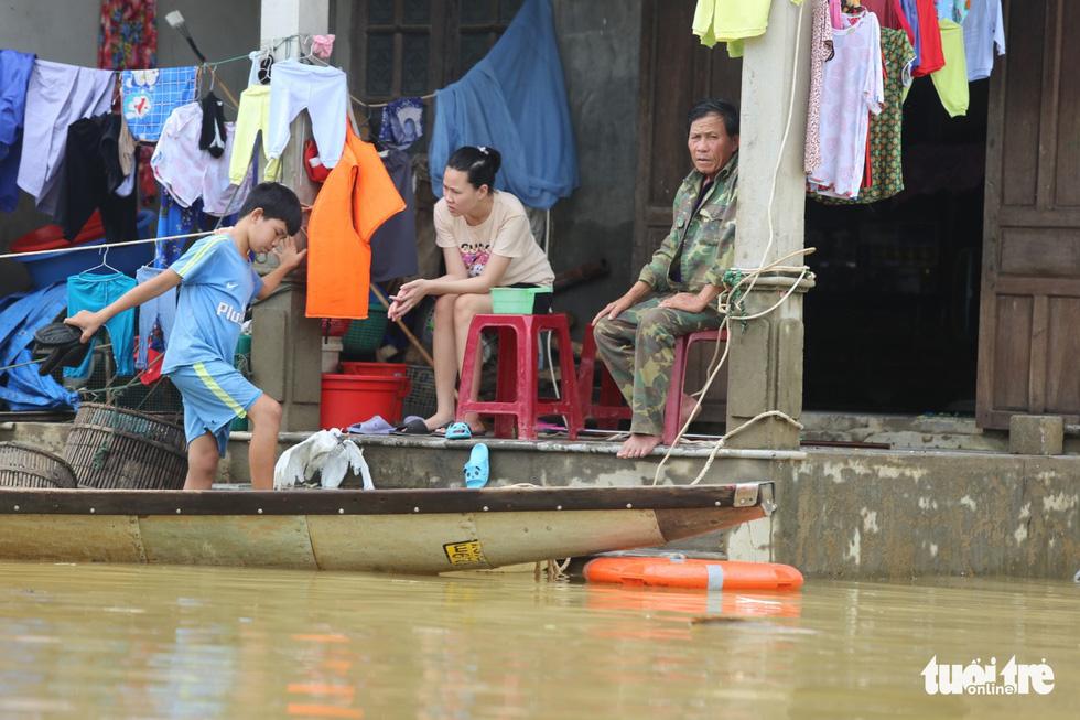 Huế nhiều xã vẫn ngập sâu, người dân chèo thuyền đi nhận cứu trợ - Ảnh 1.
