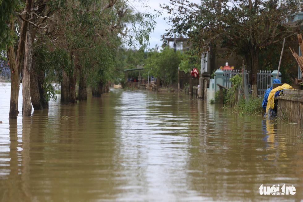 Huế nhiều xã vẫn ngập sâu, người dân chèo thuyền đi nhận cứu trợ - Ảnh 10.