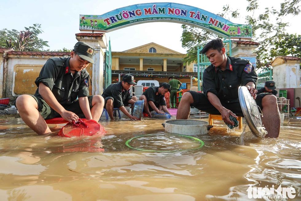 Cả đoàn xe chở cảnh sát cơ động tỏa vào vùng lũ quét dọn, hút nước giúp dân - Ảnh 1.
