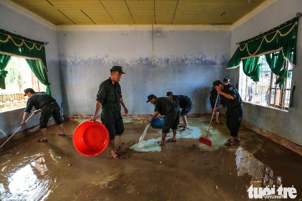 Cả đoàn xe chở cảnh sát cơ động tỏa vào vùng lũ quét dọn, hút nước giúp dân - Ảnh 2.