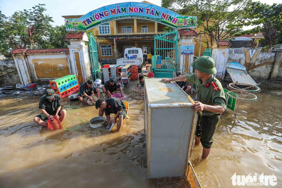 Cả đoàn xe chở cảnh sát cơ động tỏa vào vùng lũ quét dọn, hút nước giúp dân - Ảnh 3.