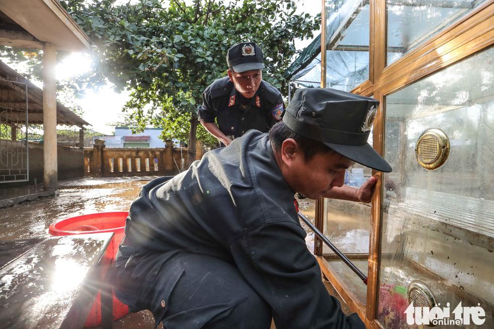 Cả đoàn xe chở cảnh sát cơ động tỏa vào vùng lũ quét dọn, hút nước giúp dân - Ảnh 5.