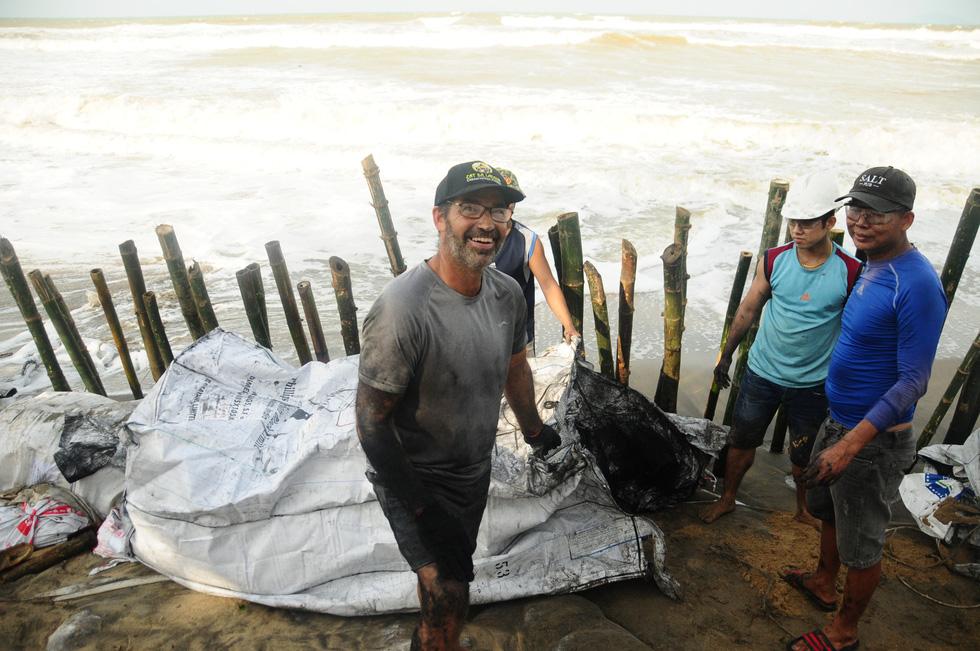 Hàng chục khách Tây vác cát, đắp đê cùng người Hội An giữ bờ biển - Ảnh 1.
