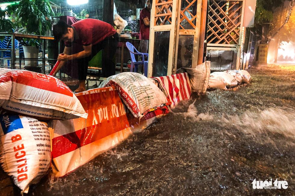 Mưa lớn đường Sài Gòn mênh mông dậy sóng, dân đắp đê ngăn nước - Ảnh 3.
