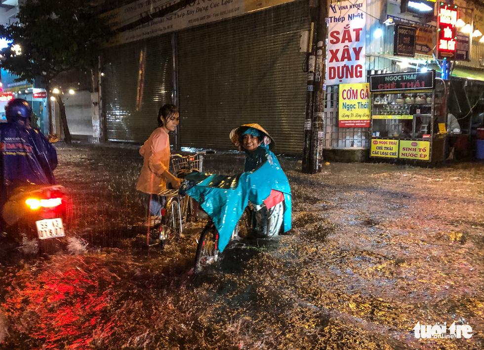 Mưa lớn đường Sài Gòn mênh mông dậy sóng, dân đắp đê ngăn nước - Ảnh 9.