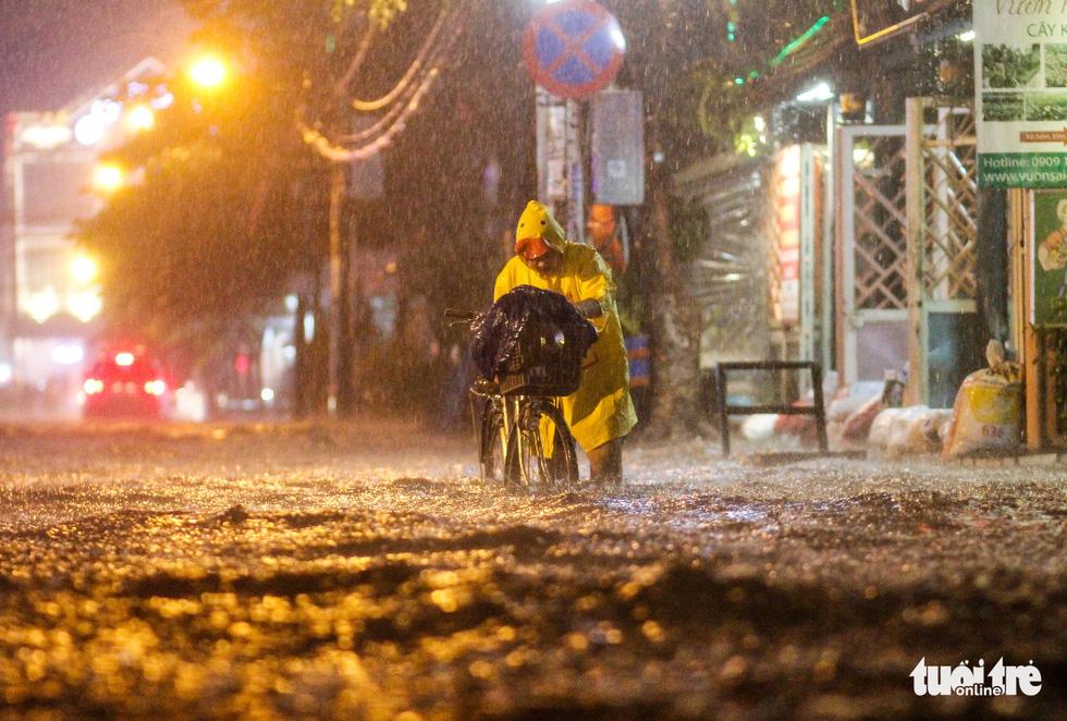 Mưa lớn đường Sài Gòn mênh mông dậy sóng, dân đắp đê ngăn nước - Ảnh 2.