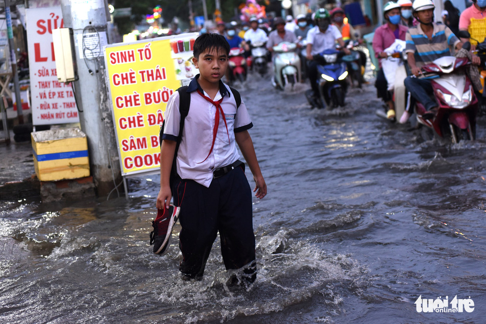 Triều cường dâng cao, học sinh, công nhân ở TP.HCM lội nước về nhà - Ảnh 1.