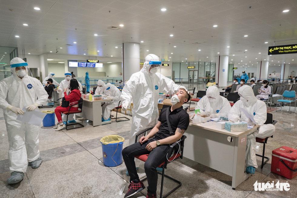 Cận cảnh việc lấy mẫu xét nghiệm COVID-19 tại sân bay Nội Bài - Ảnh 10.