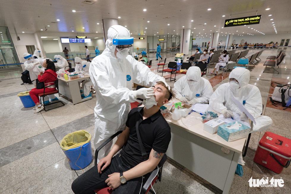 Cận cảnh việc lấy mẫu xét nghiệm COVID-19 tại sân bay Nội Bài - Ảnh 1.