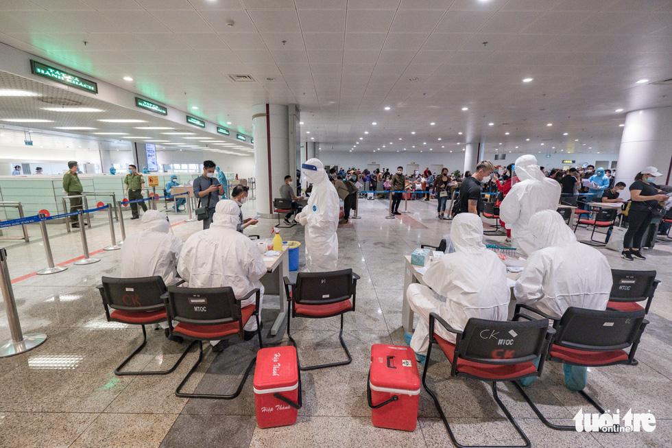 Cận cảnh việc lấy mẫu xét nghiệm COVID-19 tại sân bay Nội Bài - Ảnh 9.