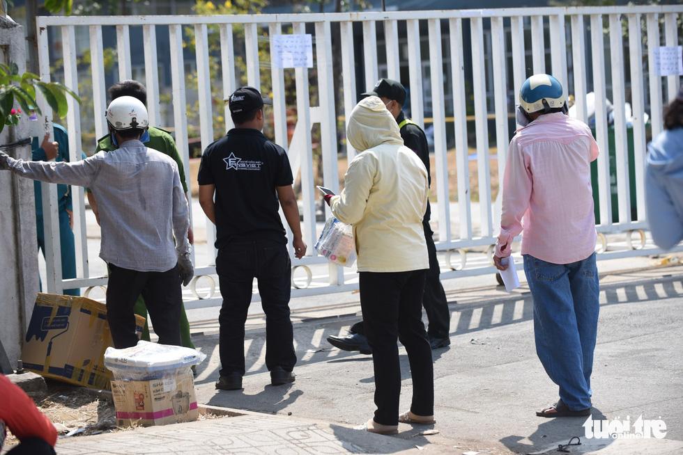 Người dân tìm cách ném hàng qua hàng rào bất chấp lệnh ngưng tiếp tế - Ảnh 6.