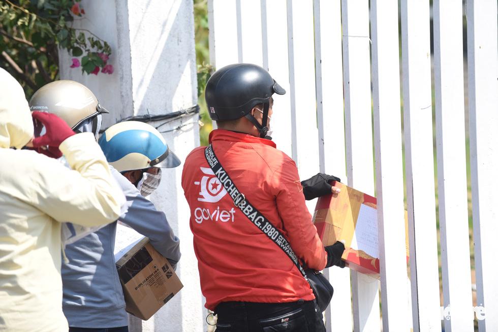 Người dân tìm cách ném hàng qua hàng rào bất chấp lệnh ngưng tiếp tế - Ảnh 7.