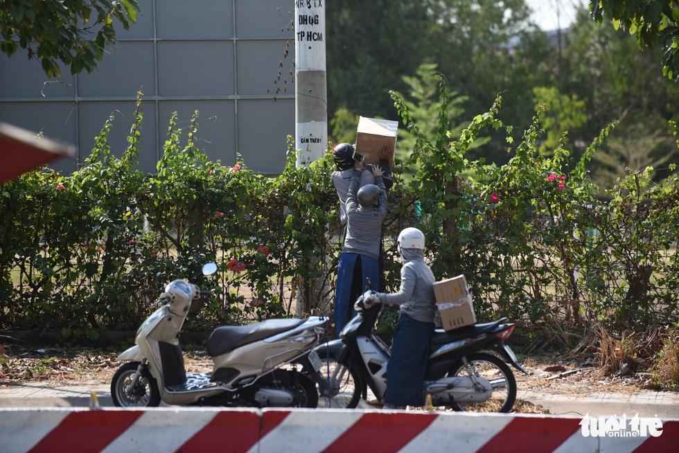 Người dân tìm cách ném hàng qua hàng rào bất chấp lệnh ngưng tiếp tế - Ảnh 3.