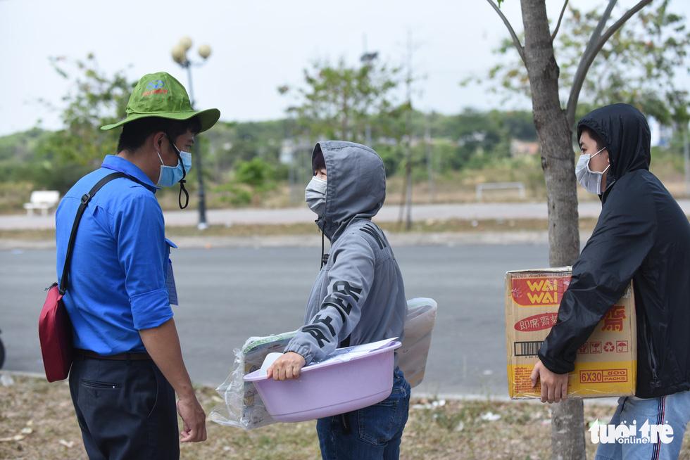Người dân tìm cách ném hàng qua hàng rào bất chấp lệnh ngưng tiếp tế - Ảnh 11.